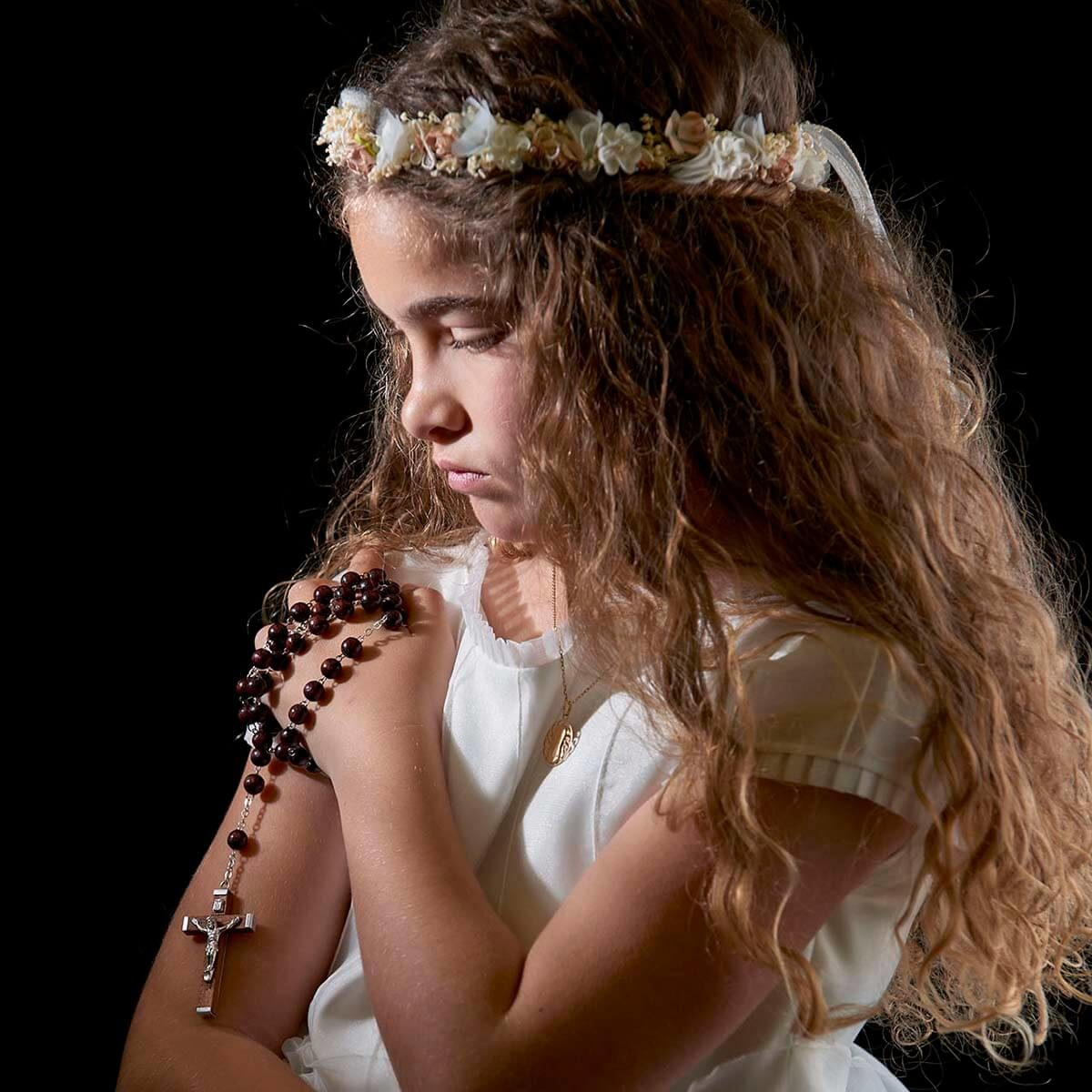 Niña mirando rosario de comunión